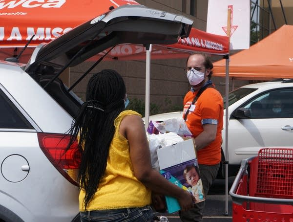 A person wearing a face mask helps load a car.