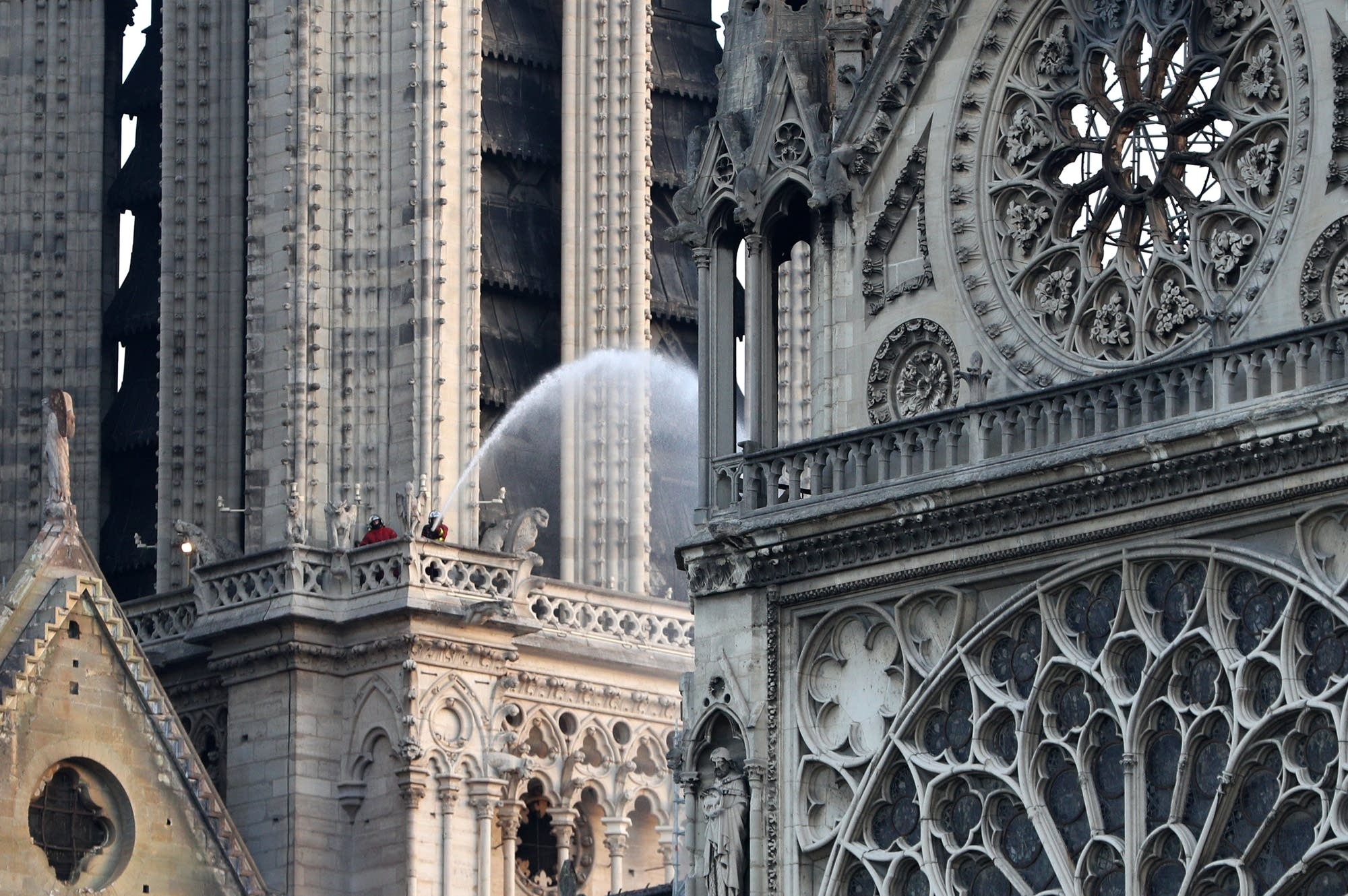 A firefighter hoses down a section of the Notre Dame cathedral.