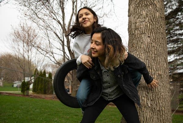 two people in front of a tree and tire swing