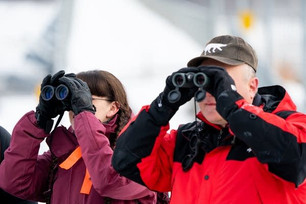 Two people look through binoculars.