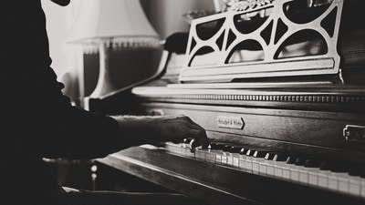 55a794 20190624 black and white photo of person playing piano