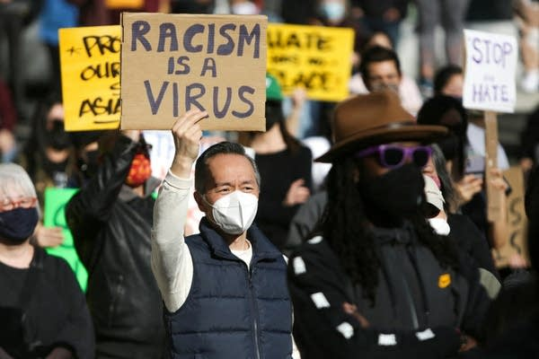 """A man holds a sign that says """"Racism is a virus."""""""