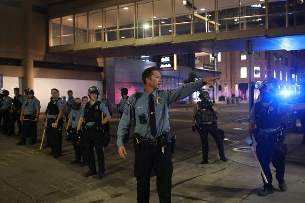 A police officer points as he stands near other officers.