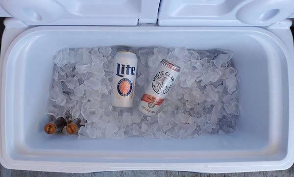 Open cooler with ice and a Miller Lite tallboy and can of White Claw