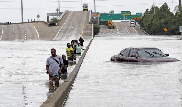 Evacuees wade down a flooded section of Interstate 610.