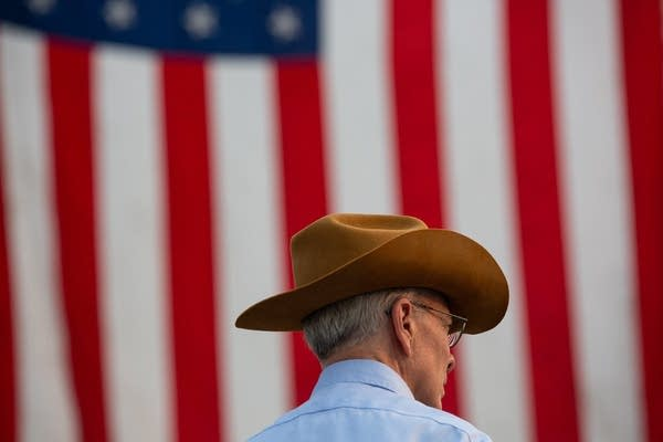 A man in a cowboy hat stands in front of a large flag.