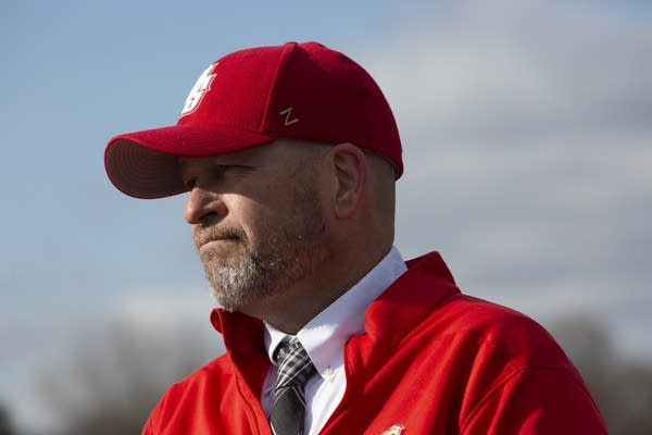 A man wearing a red baseball cap and jacket.