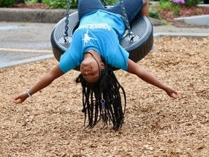 Tahjanae Ware plays on a tire swing.