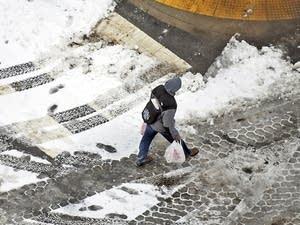 A pedestrian walks across the street in downtown Scranton, Pa.