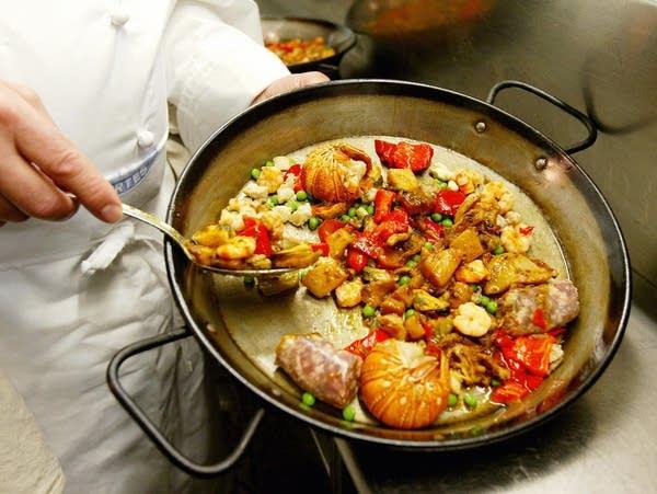 A chef prepares a seafood paella