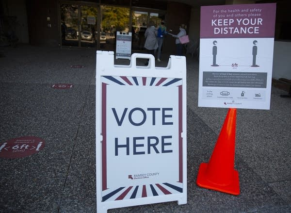 "A sign that reads ""vote here"" and a sign that reads ""keep your distance."""