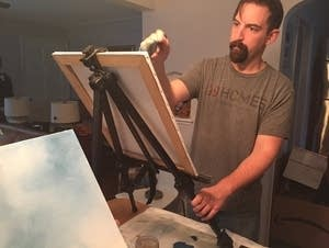 Justin Miller works on a painting.