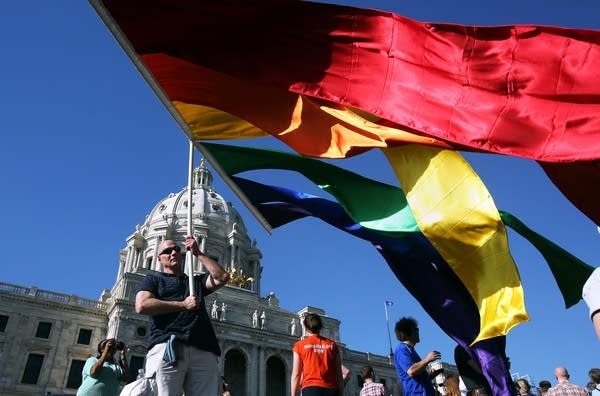 Wes Davey of St. Paul, Minn. flies a large flag in front of the Capitol after Gov. Mark Dayton signed the same-sex marriage bill into law in St. Paul, Minn. Tuesday, May 14, 2013.