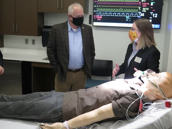 A man talks to a woman in a clinic room in front of a dummy patient.