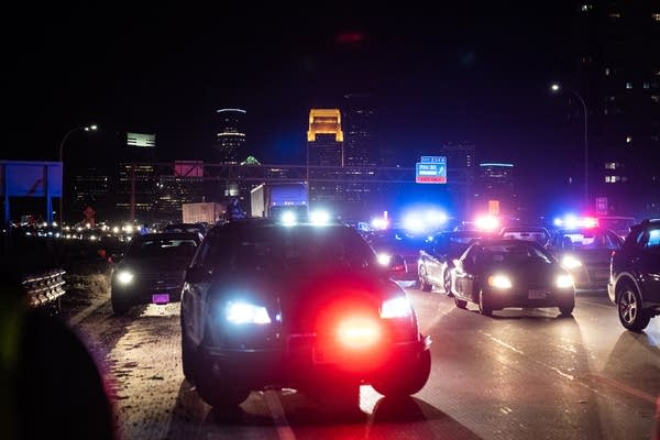 Police cars and traffic in front of a city skyline.