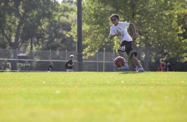 A boy wearing shorts and a t-shirt runs after a soccer ball in a field.