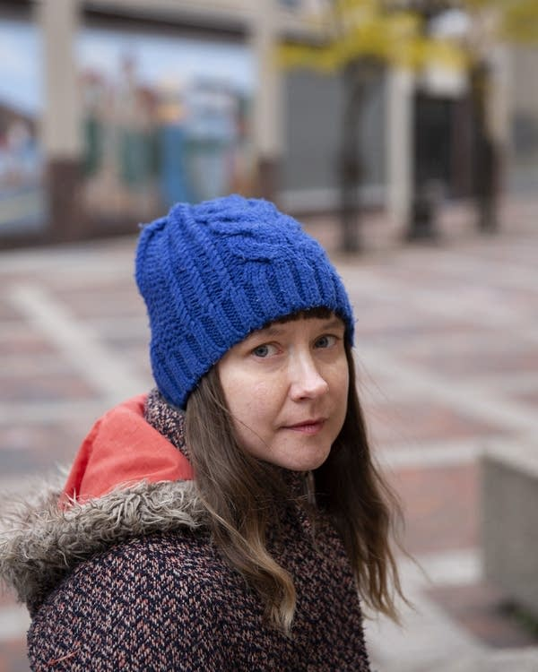 A woman wearing a blue winter hat and coat sits outside.