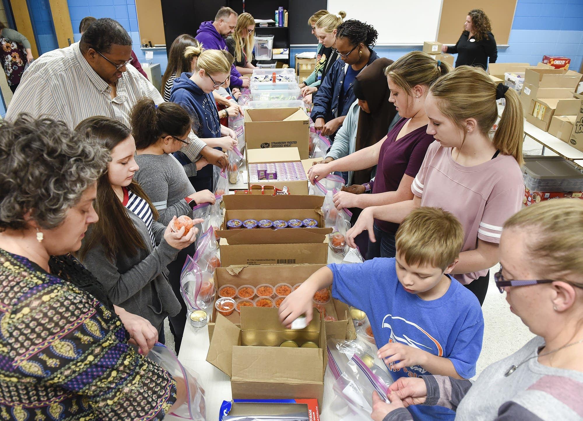 Volunteers pack weekend meals for students.