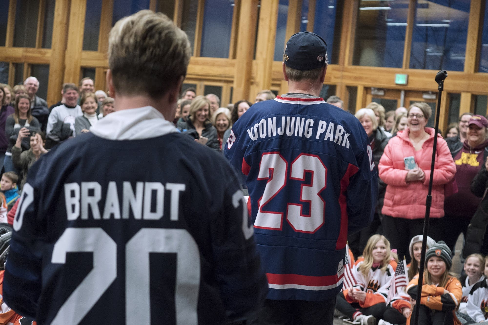 Greg, right, and Robin Brandt wear their daughters' Olympic hockey jerseys.