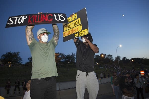 Protesters stand on the concrete barrier.