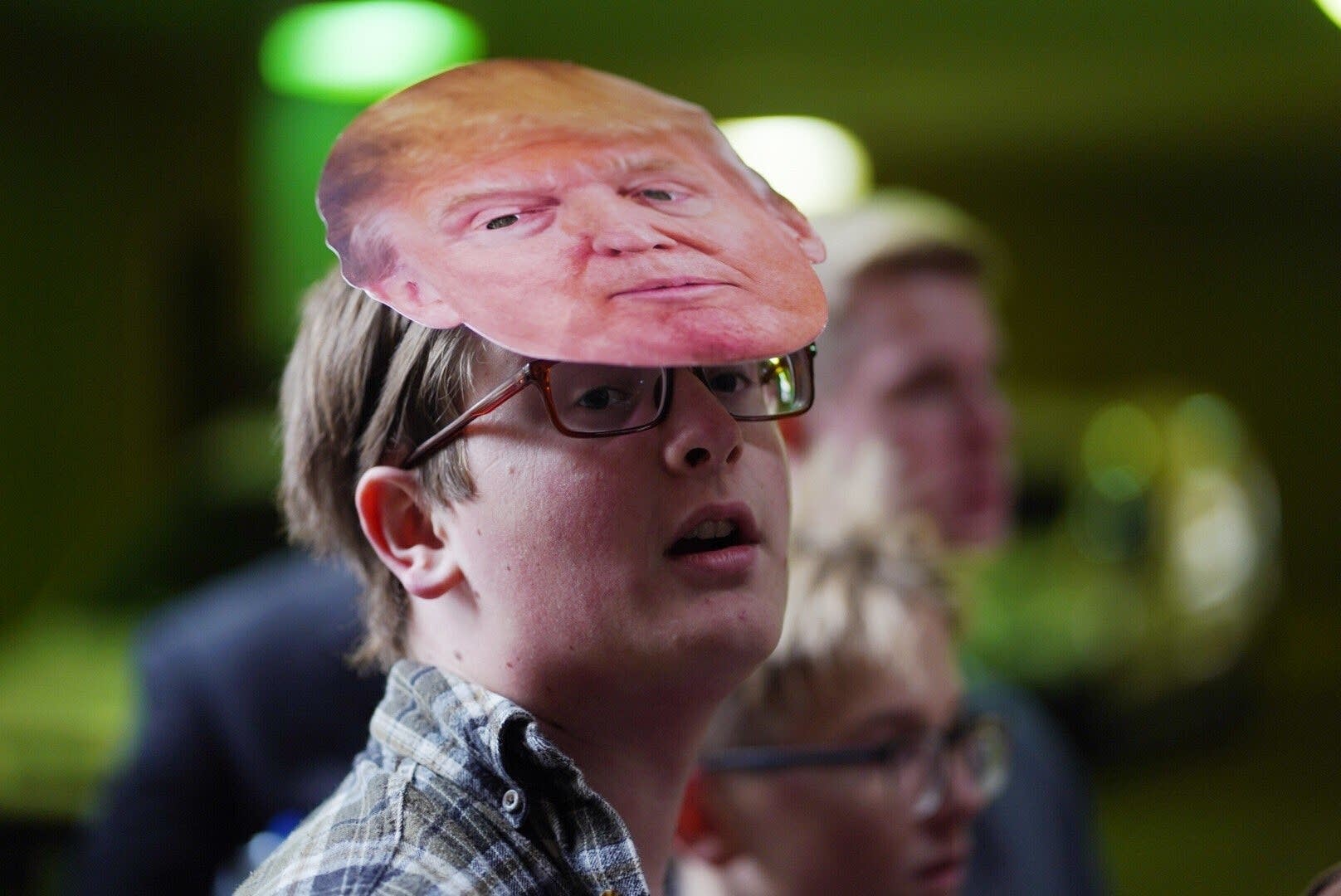 Thirteen-year-old Holden Dowd wears a Trump mask.