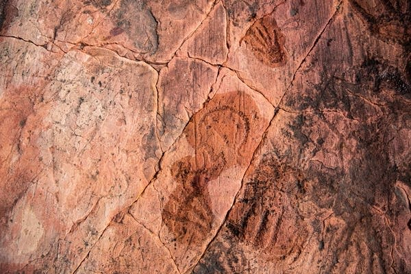 A carving of a woman figure in red rocks.