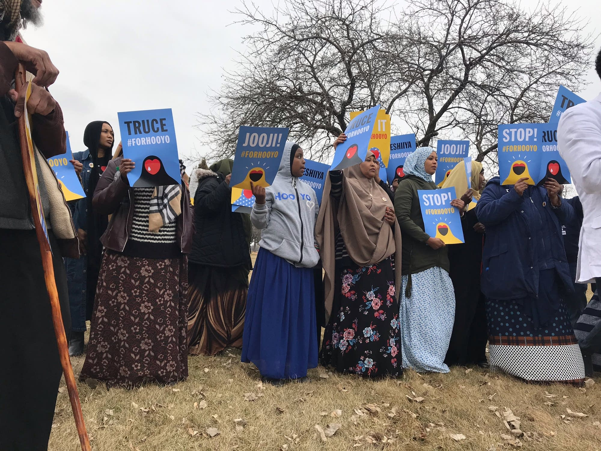 A group holds #ForHooyo signs.