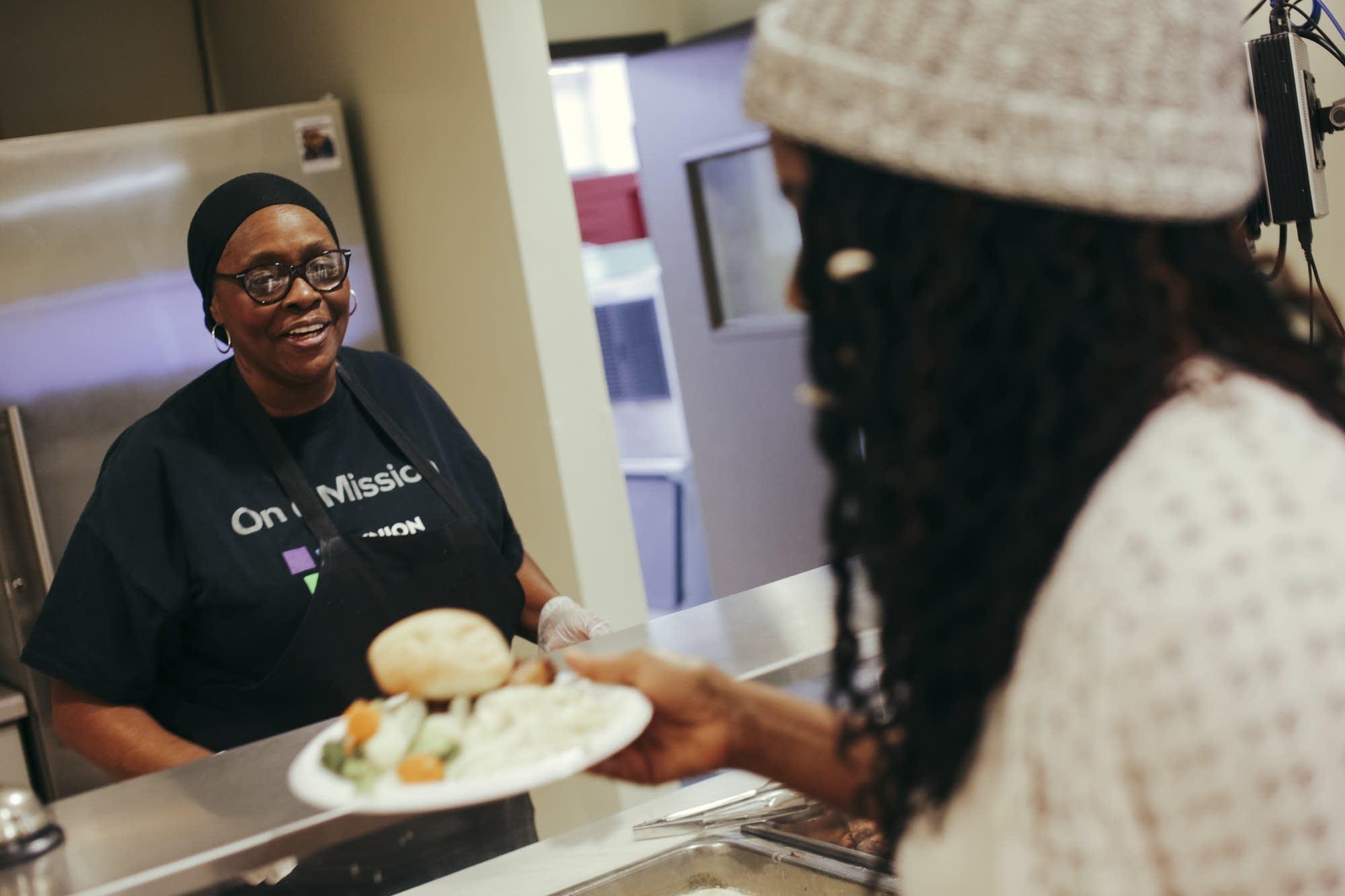 Roseline Charles serves up lunch inside of the Union Gospel Mission
