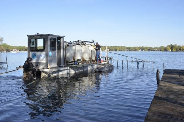 Crews fill a tanker barge with aluminum sulfate on Bass Lake.
