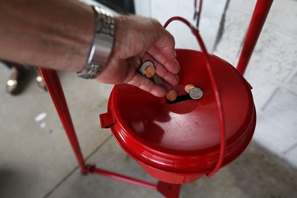 A donation is made into a Salvation Army red kettle.