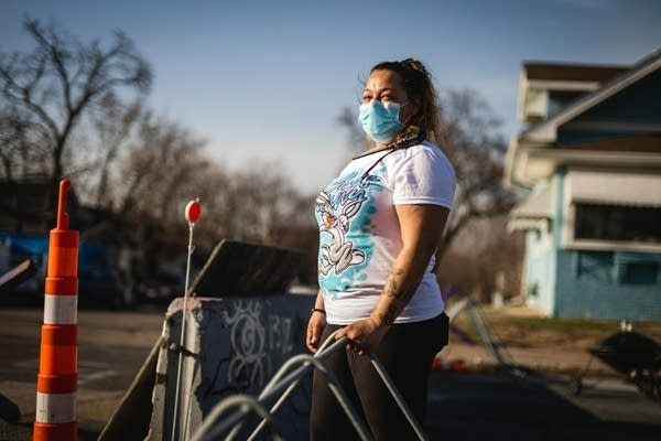 A woman stands at a barricade.