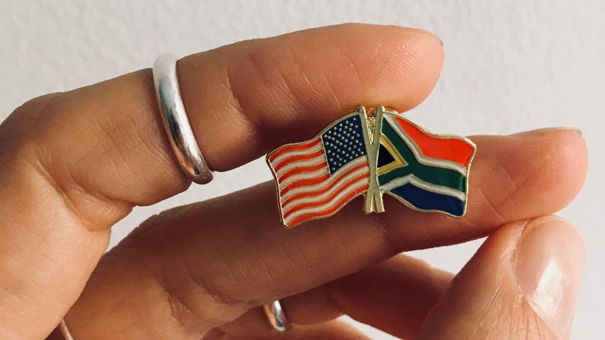 Dessa holds a pin showing the U.S. and South African Flags