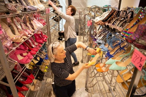 Michelle Keefe and Nancy Corcoran sort shoes by size and color.