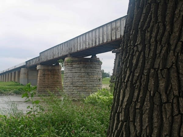 a stone and steel railroad bridge over a river