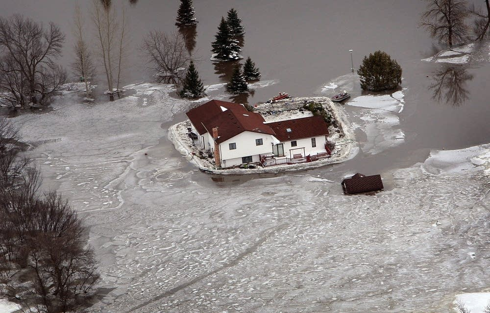 A lone house sits surrounded by ice and water