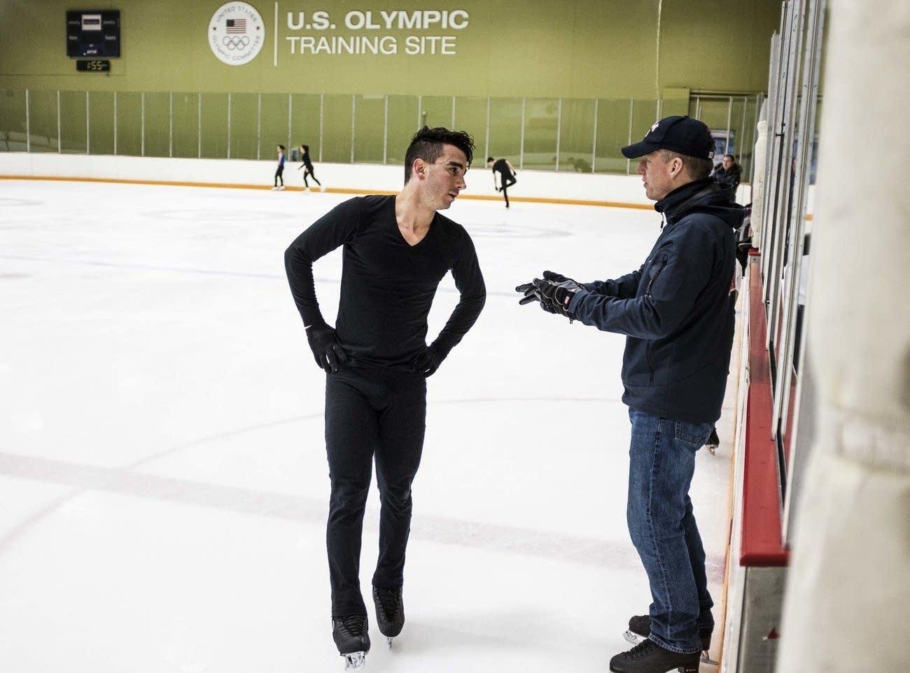 Max Aaron talks with his coach, Tom Zakrajsek, during practice