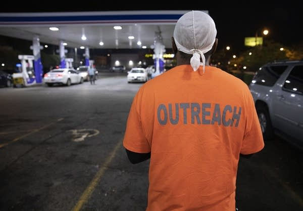 """A man faces a gas station. The back of his orange shirt reads """"outreach."""""""