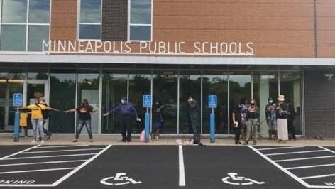 A group of people stand outside of a school