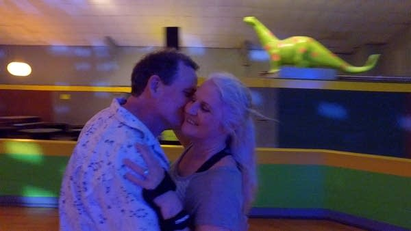 Two people skate in a roller rink.