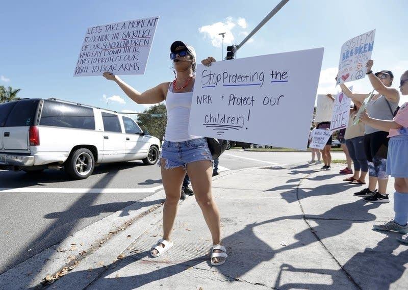 Juliana Cruz holds an anti-gun sign in Parkland, Fl., on February 17, 2018