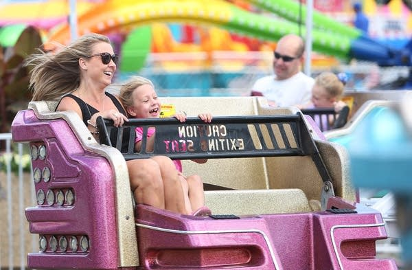 A woman and girl laugh on a ride.