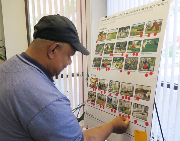 A man puts a sticker on a board with pictures of apartment features.