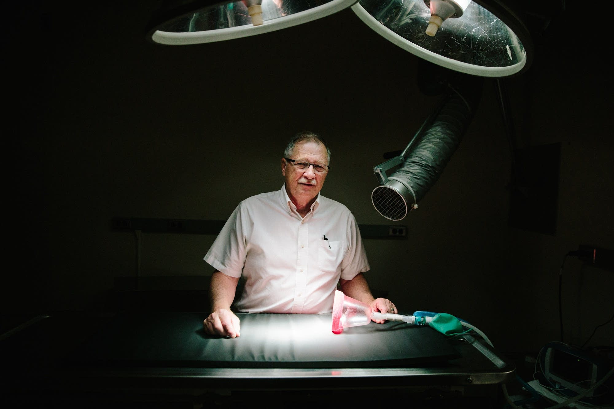 Dr. Patrick Redig stands for a portrait next to an operating table.