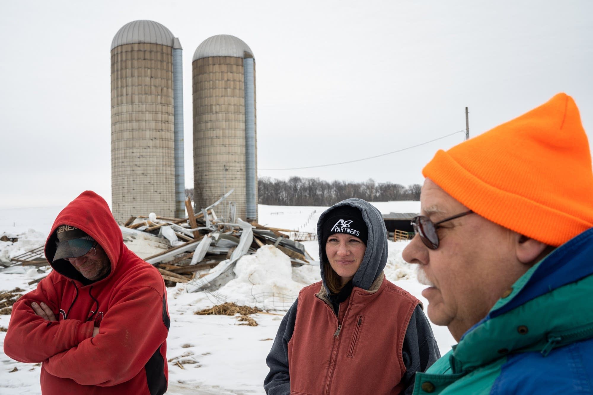 Dave Alberts, Laura Alberts and John Bierbaum stand near a collapsed barn.
