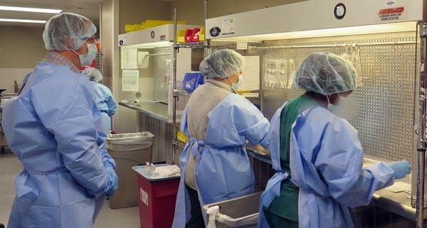Pharmacy technicians prepare IV bag solutions.
