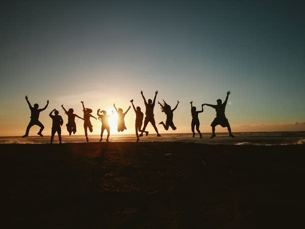 A silhouette of a group of people jumping during a sunset.
