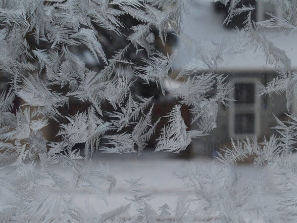 Frost forms on a window as temperatures dip below zero.