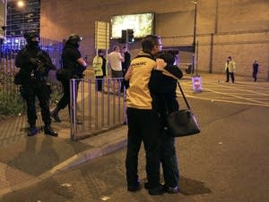 Armed police stand guard at Manchester Arena after reports of an explosion.