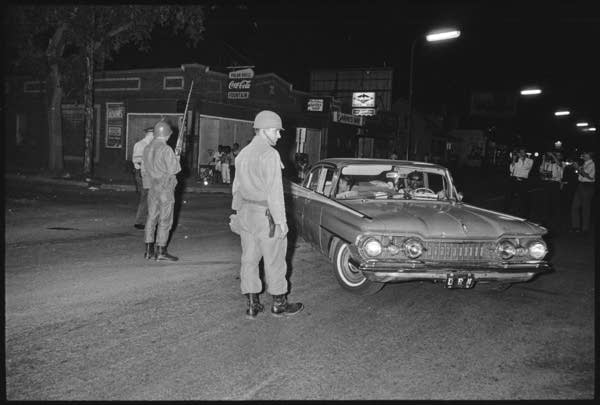 National Guard members stand next to a pulled over car.