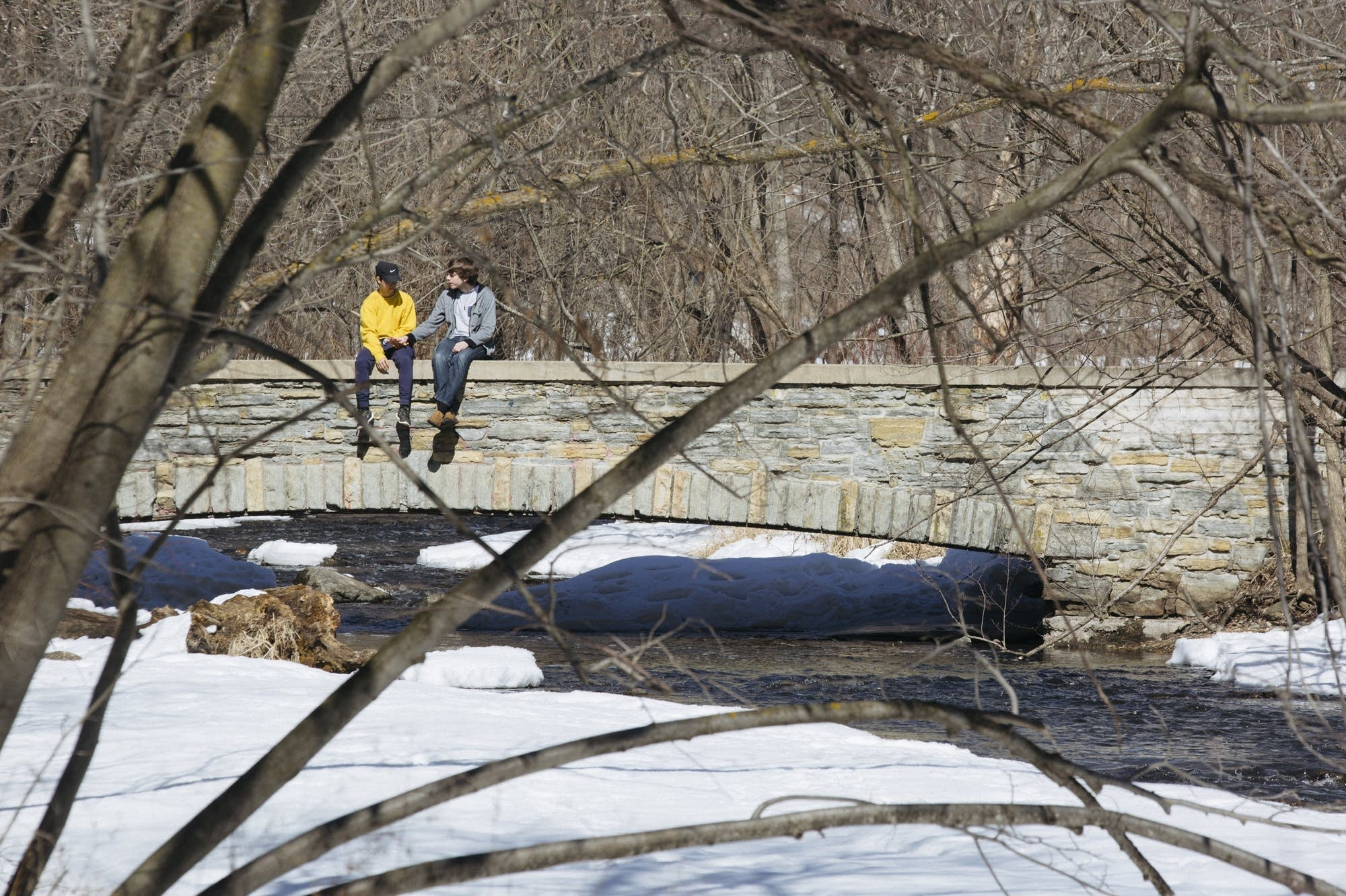Two people share a moment on a bridge over Minnehaha Creek